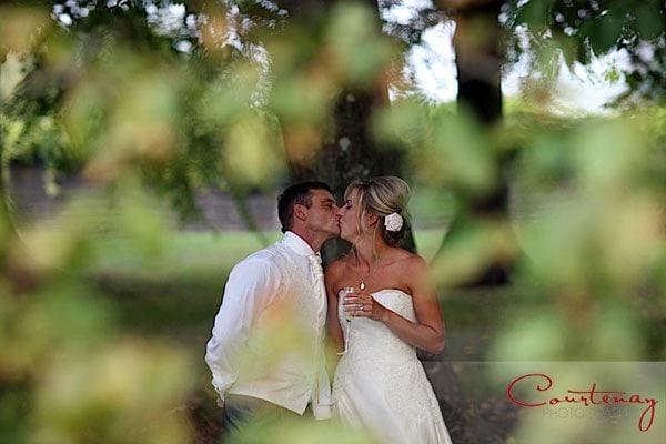 bride groom sneaky kiss under tree