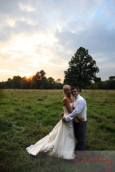bride and groom hug in fields at sunset