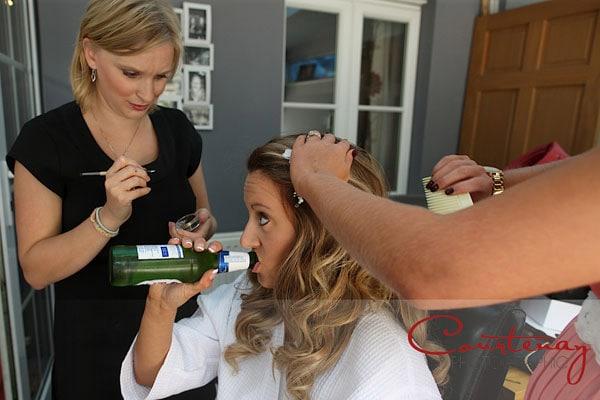 bride drinks beer as hair is done