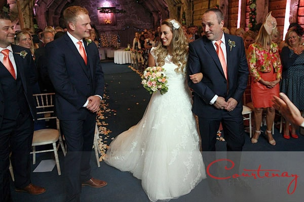 bride grins at groom as she arrives at fornt of aisle