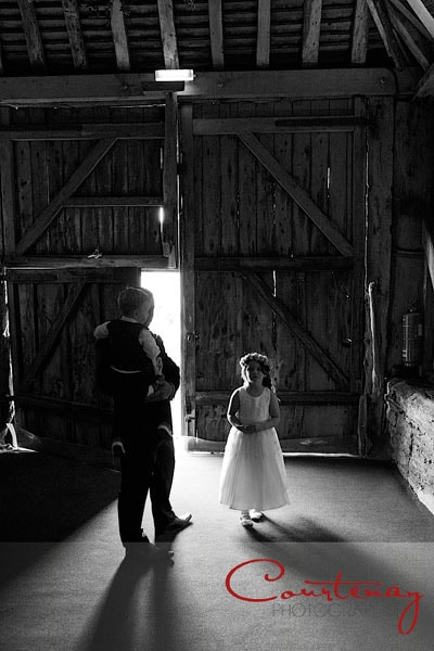 beautiful photograph small bridesmaid in front of large wooden barn doors