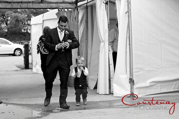 funny toddler and dad walk at wedding