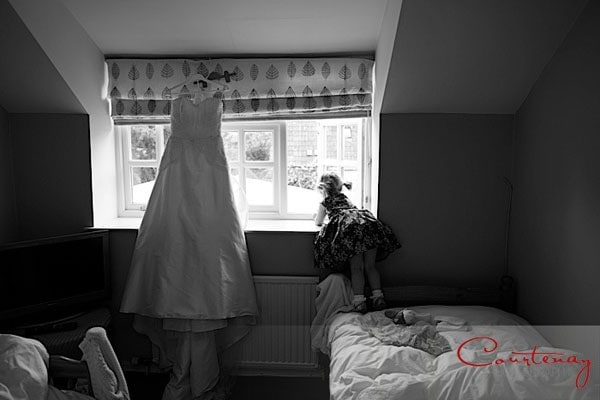 toddler with wedding dress in window
