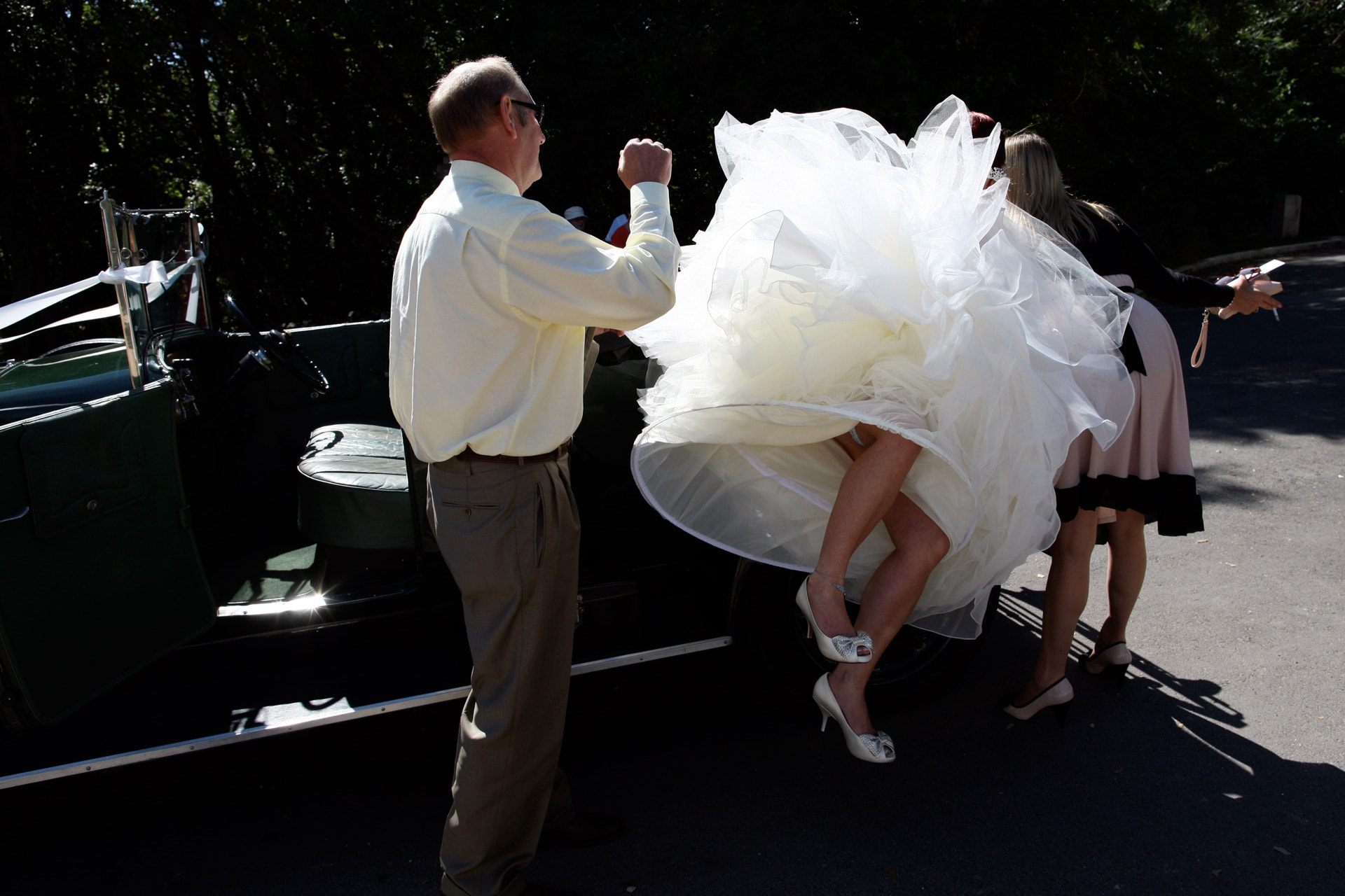 bride-tipping-up-skirt-in-car