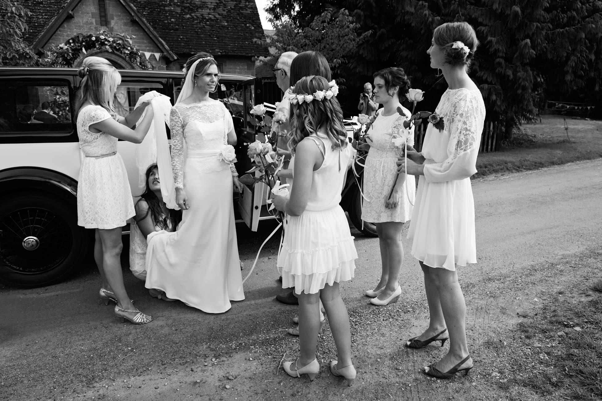 bridesmaid-adjusts-wedding-dress