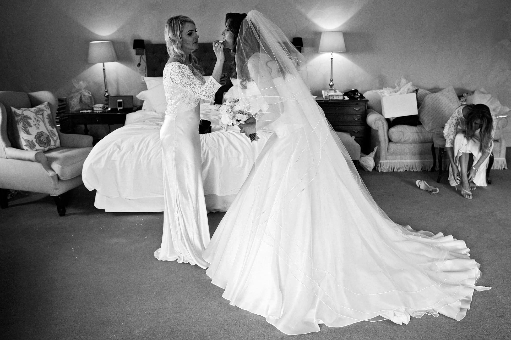 bridesmaid-applies-lipstick-to-bride
