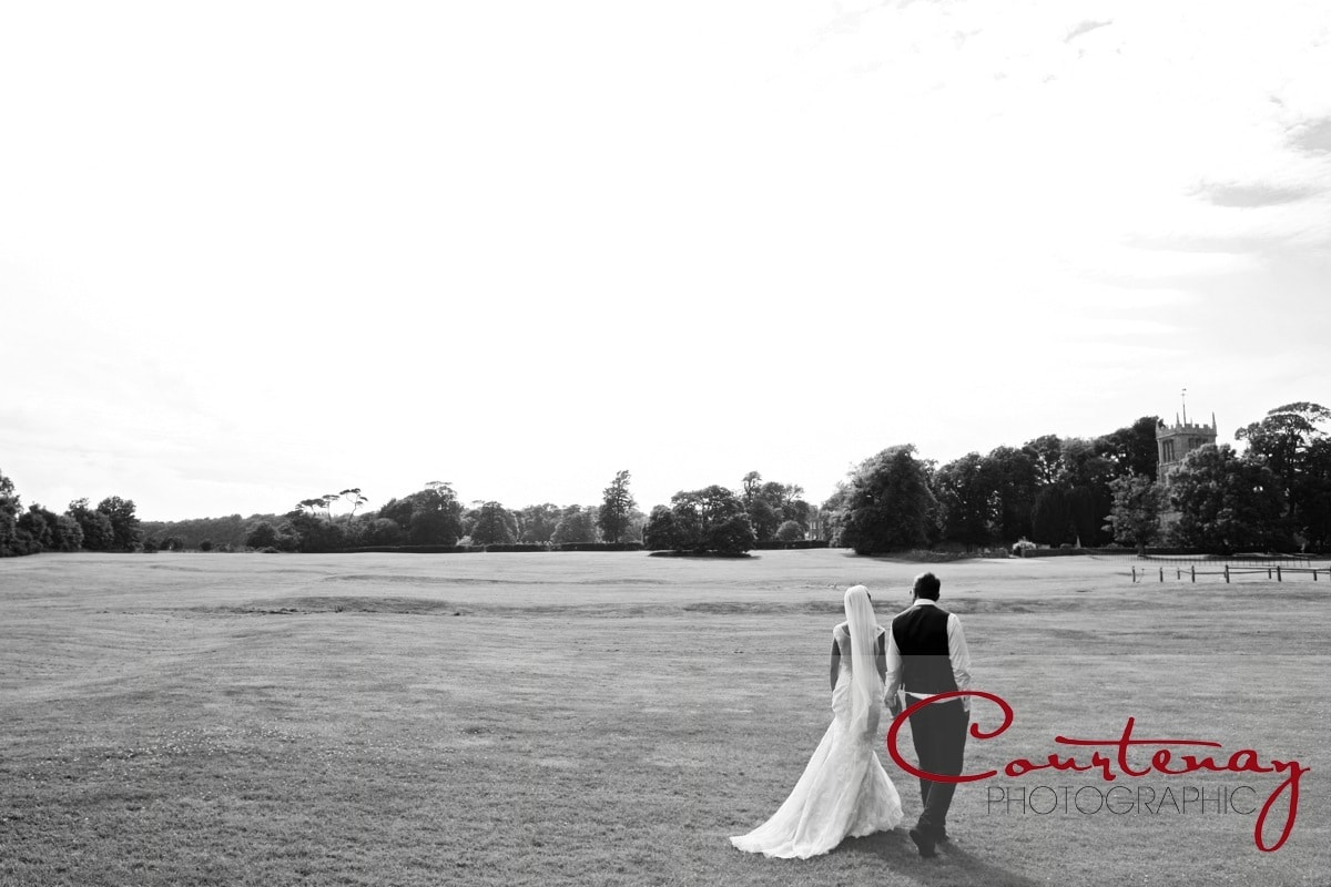 couple walk across estate grounds