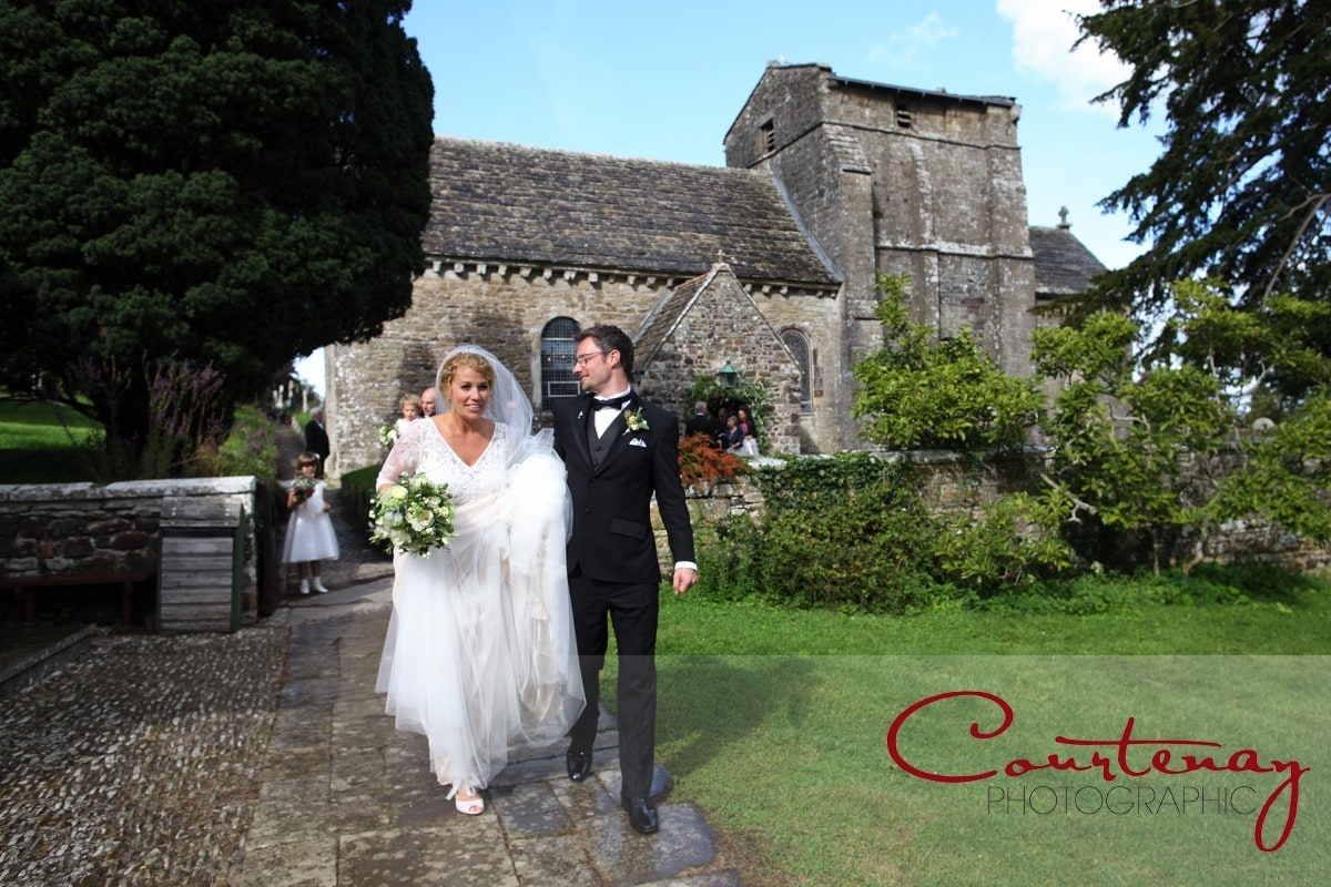 bride and groom exit the churchyard
