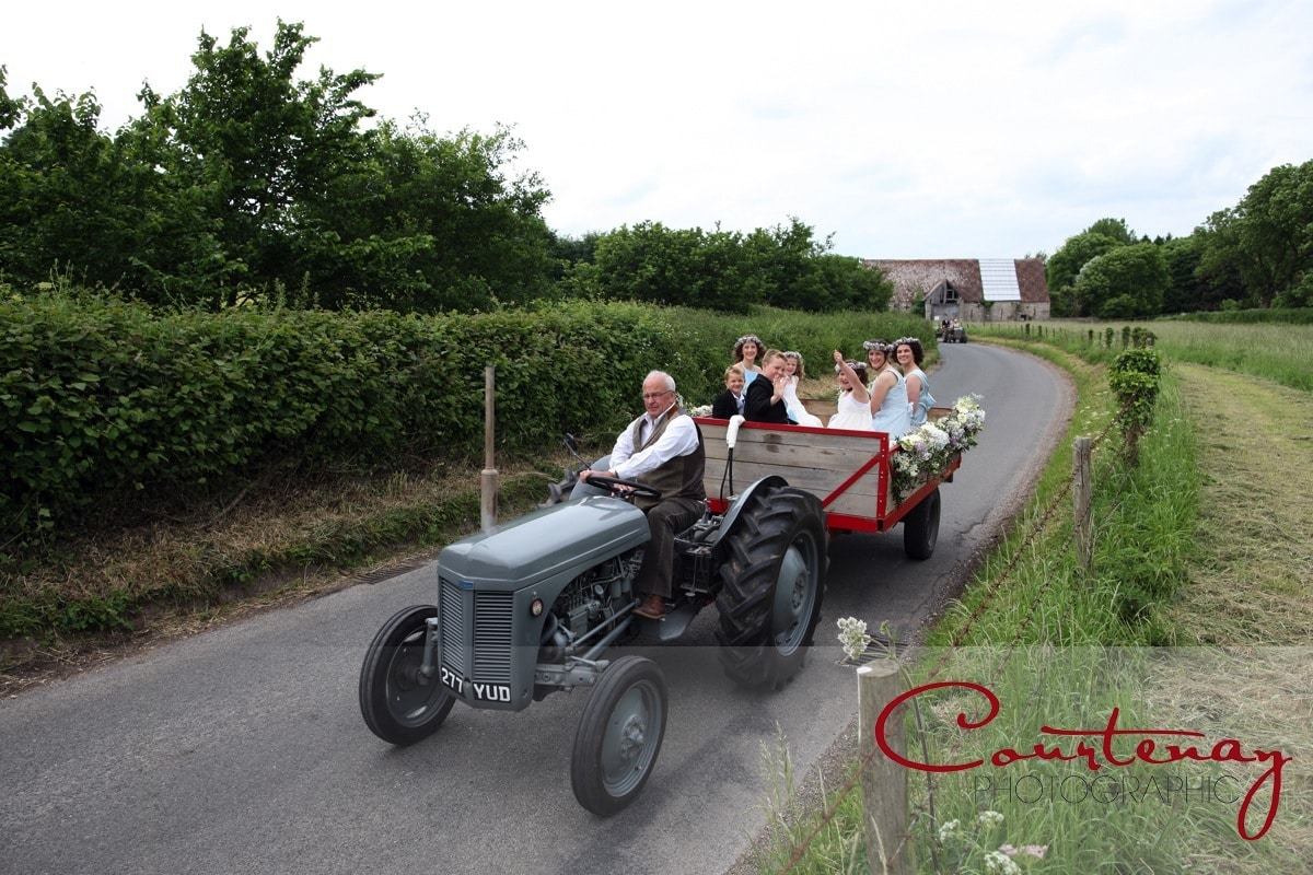 bridesmaids riding behind a tractor