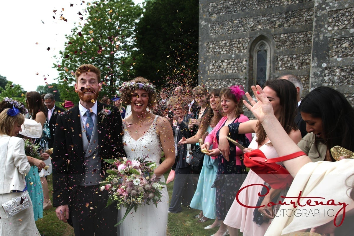 bride and groom walk through a tunnel of confetti