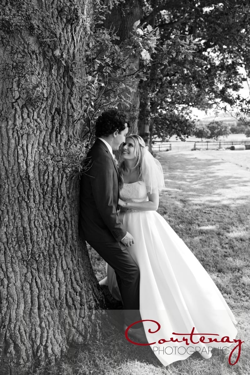 bride and groom stop to lean on a tree