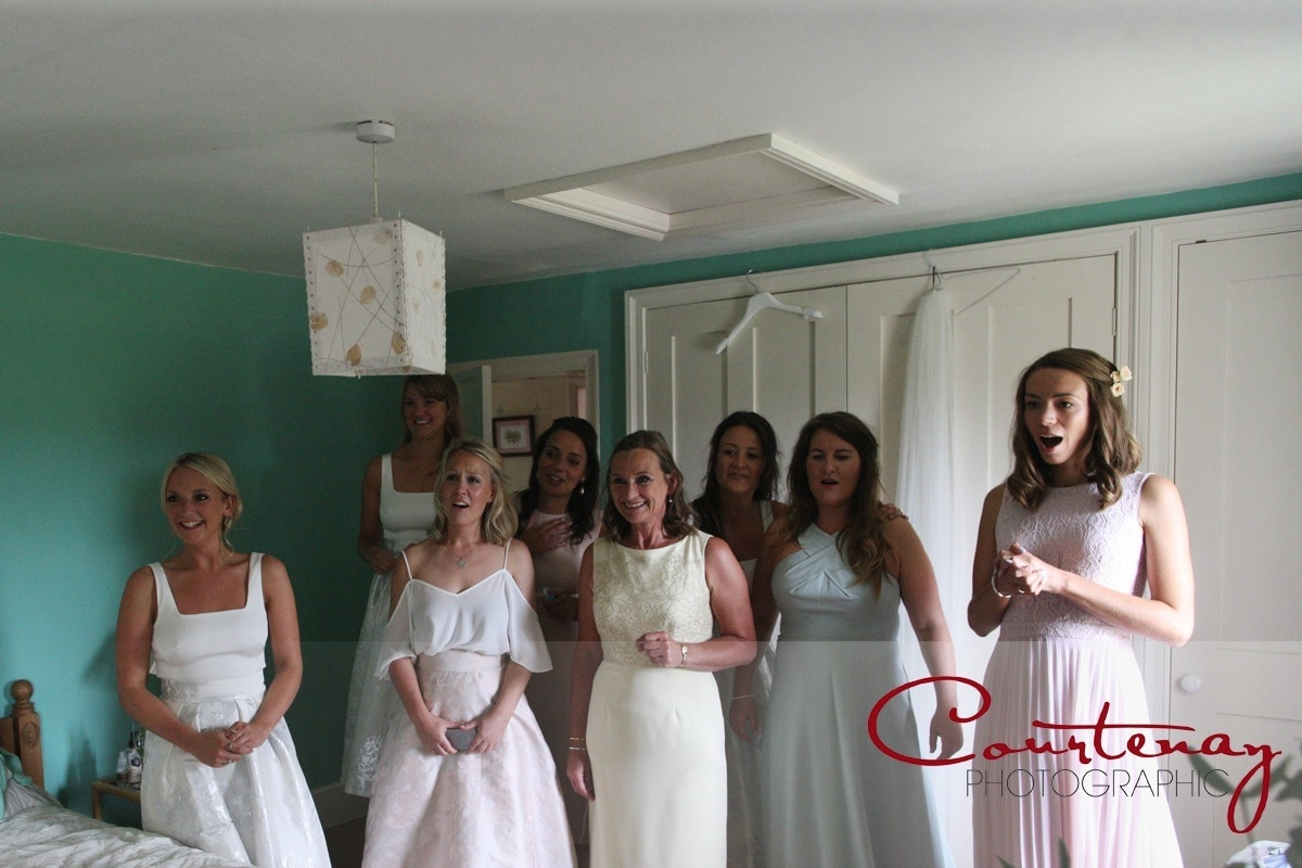 bridesmaids see bride in her dress for the first time