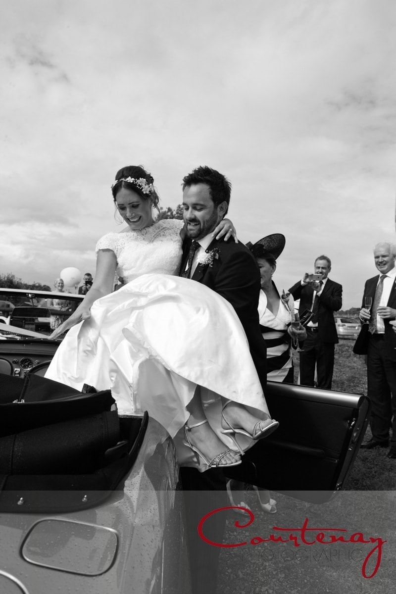groom lifts his bride from vintage car