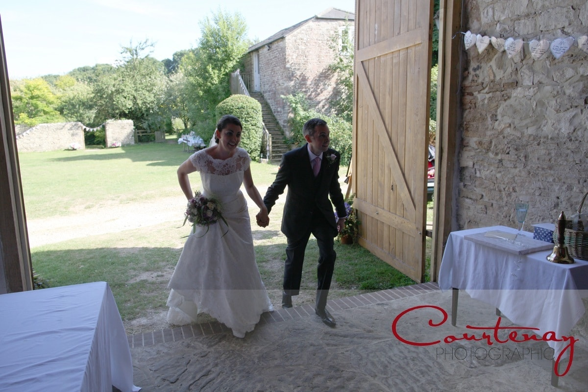 bride and groom enter the barn