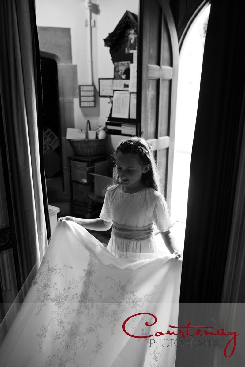 bridesmaid holds the brides dress