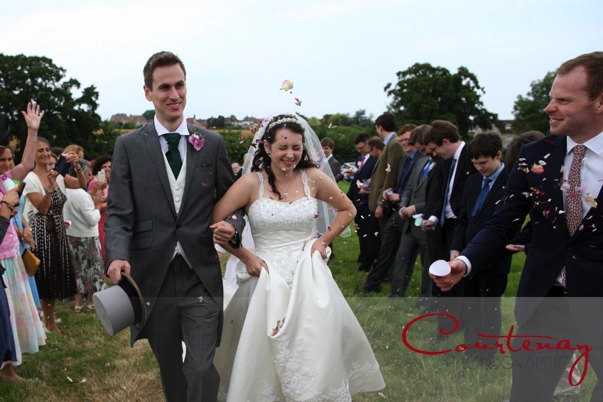 bride and groom walk through confetti tunnel