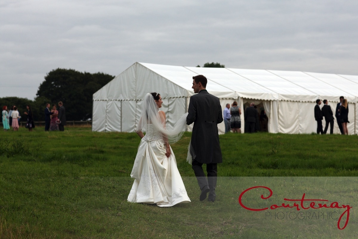 bride and groom head back to marquee