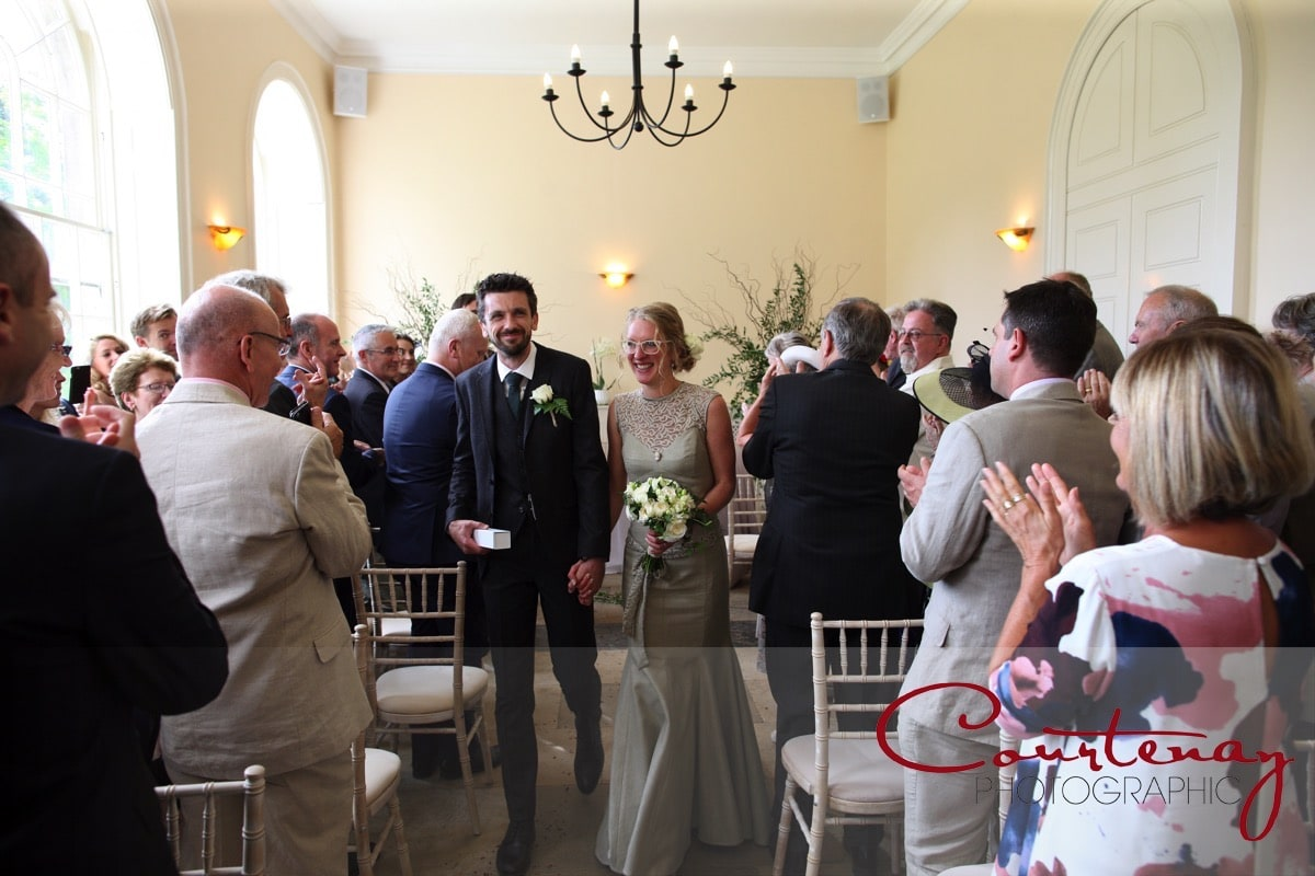 bride and groom exit the orangery