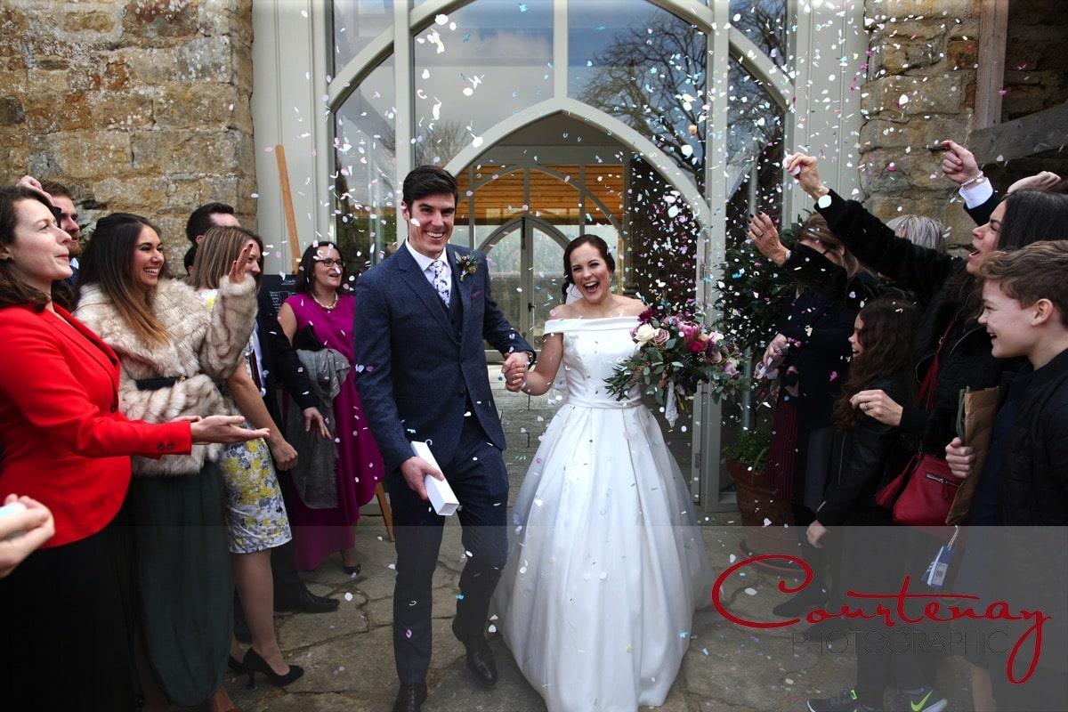 newlyweds walk through confetti tunnel