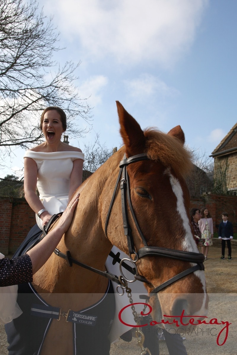 bride rides her horse at drinks reception