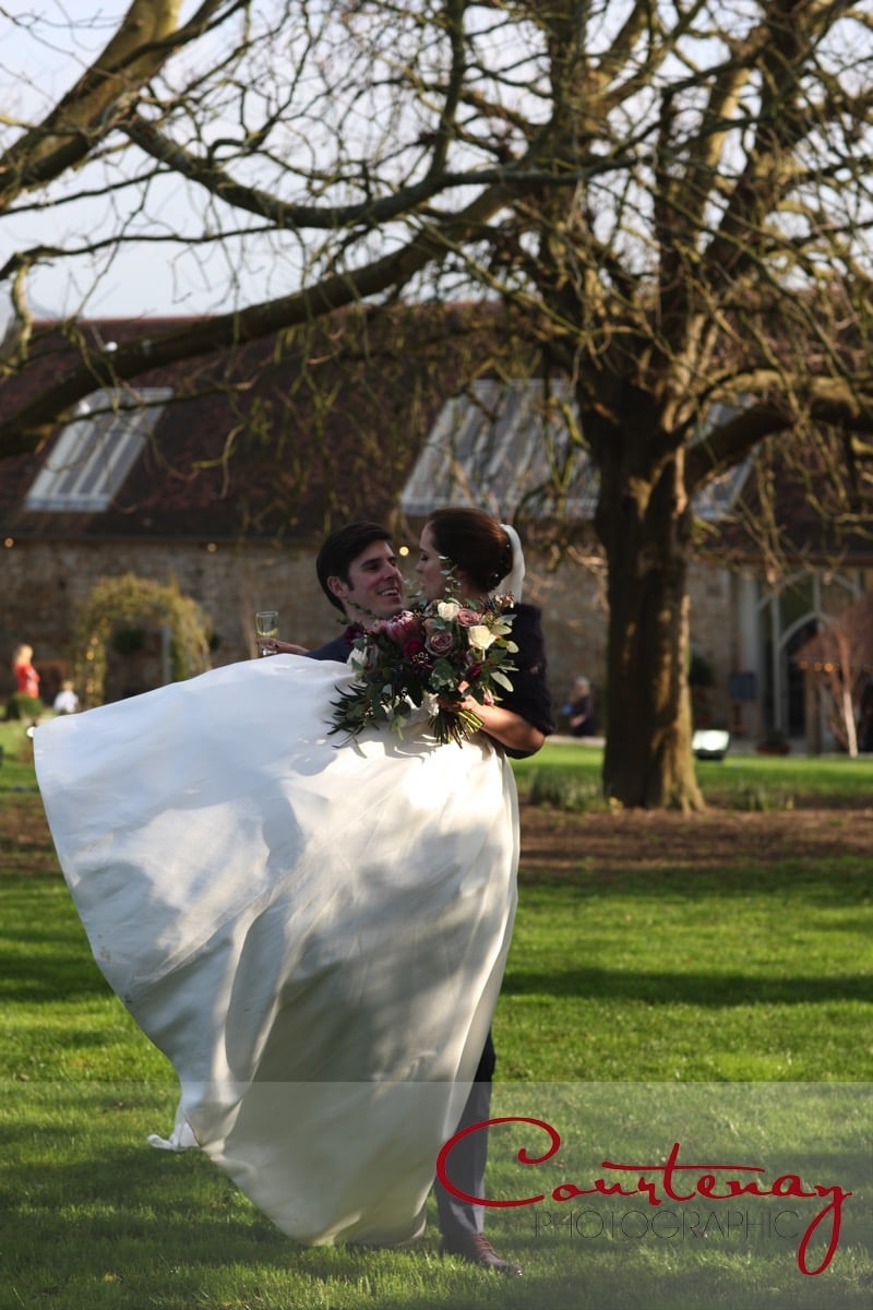 groom carries bride accross the grass