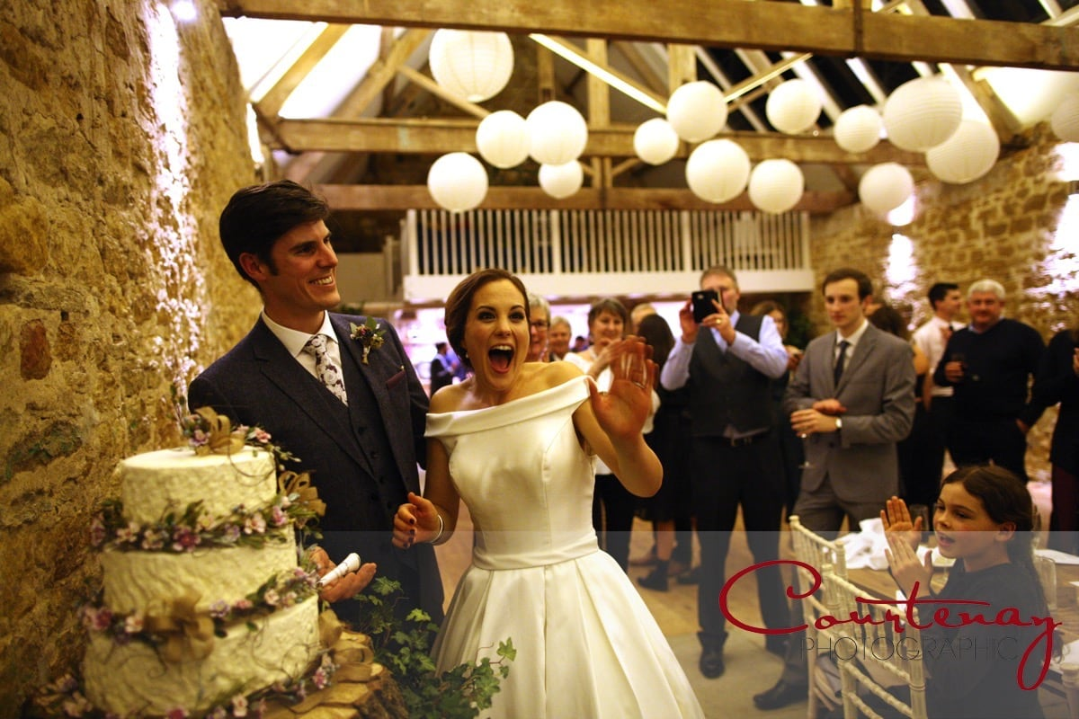 cutting the wedding cake in front of family and friends