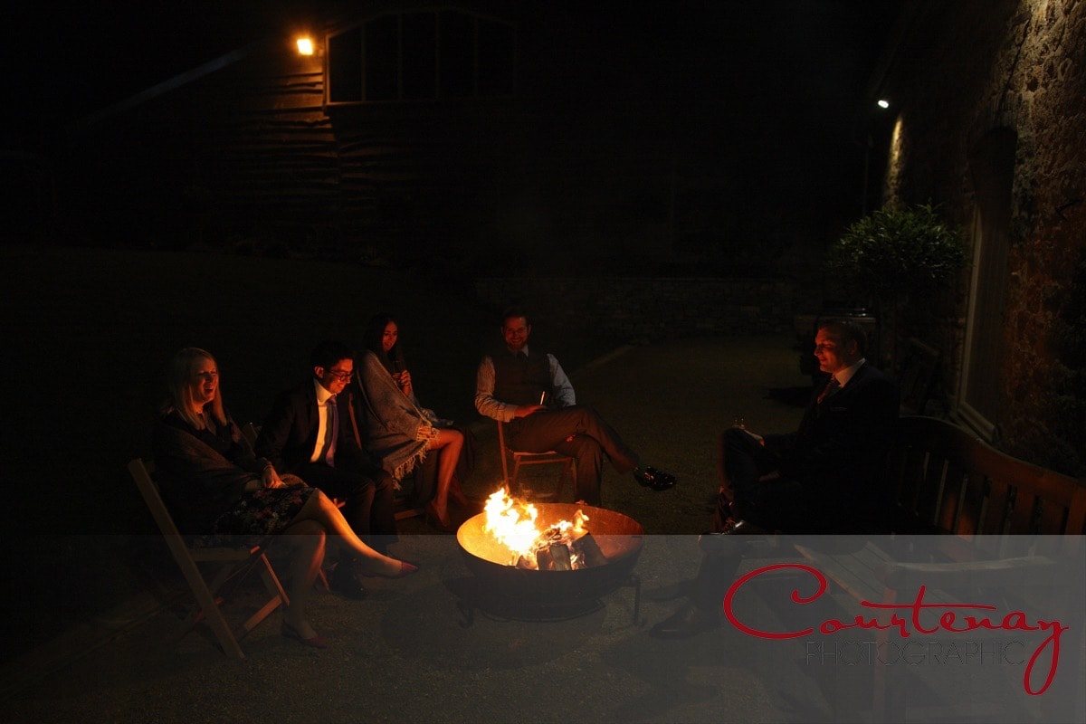 guests warm themselves by the fire pits