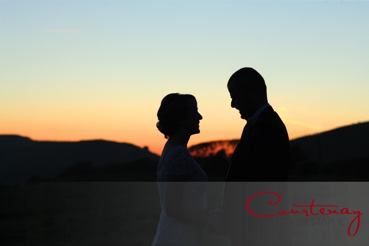 bride and groom take romantic sunset walk