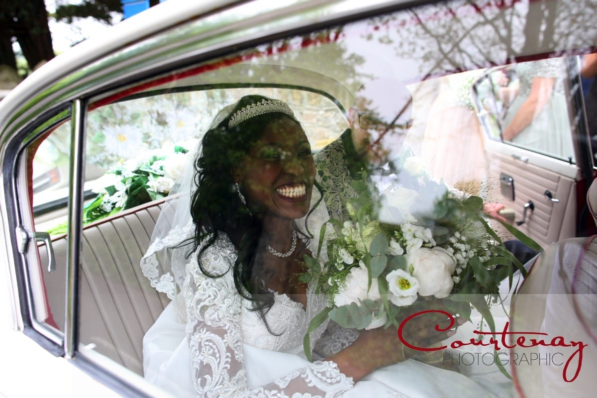 bride happily grins out of wedding car window