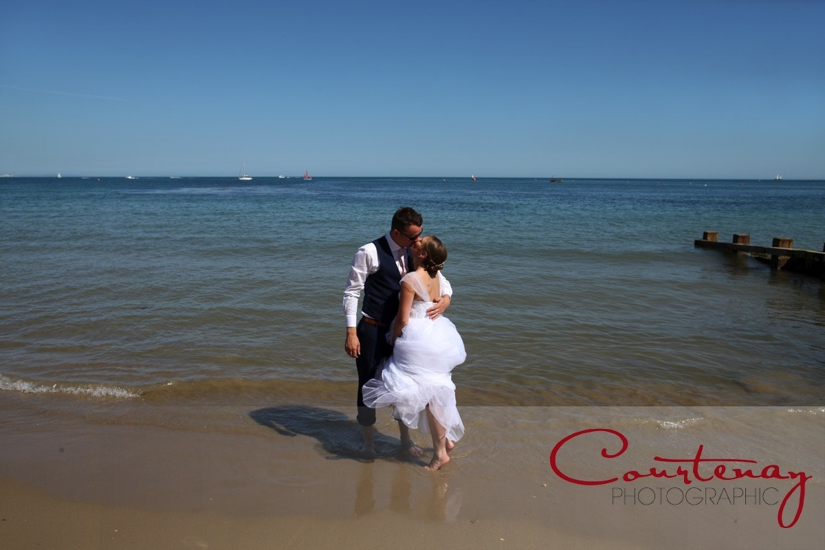 bride and groom enjoy the cool sea