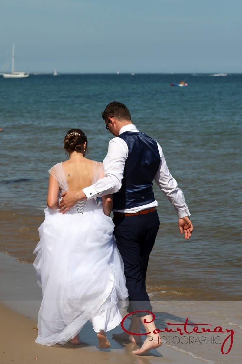 bride and groom stroll along the beach