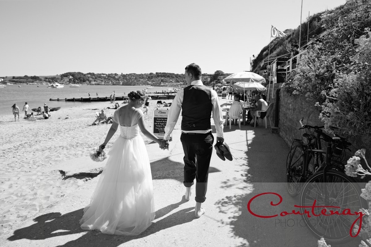 bride and groom stroll along the promenade at Swanmage on their Grand Hotel Wedding day