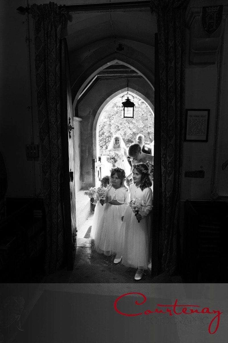 bridesmaids peek inside the church