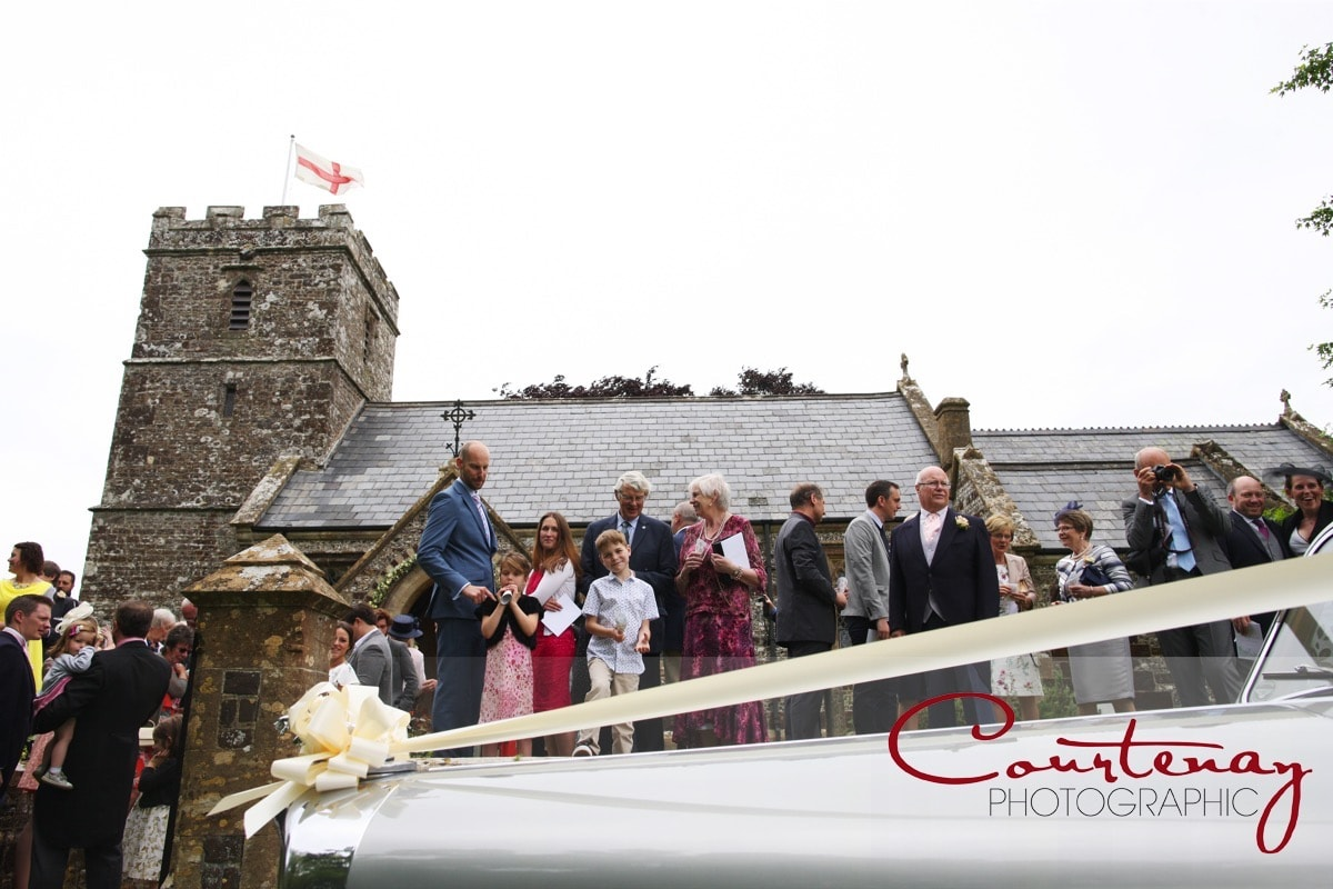 outside the church guests watch the happy couple leave