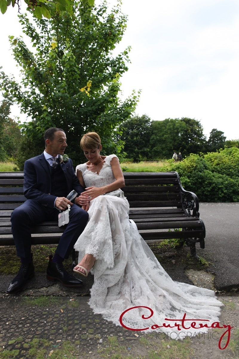 bride and groom sit on a park bench