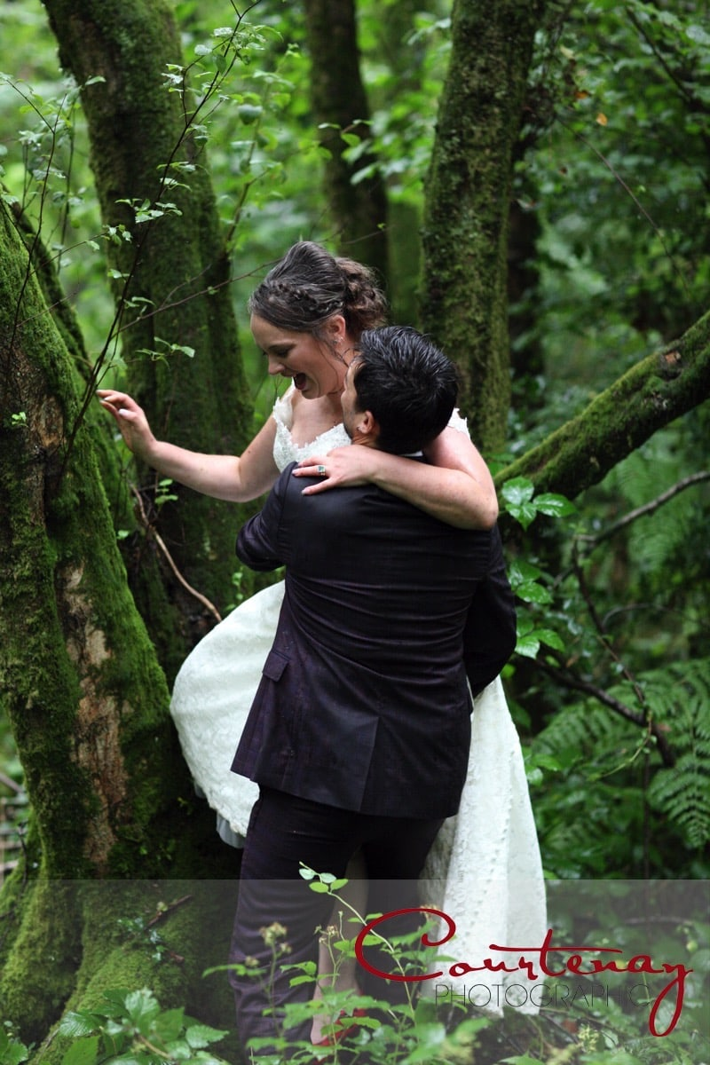 groom helps bride out of a tree